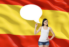 Woman is pointing out the empty thought bubble. Spanish flag as a background. Royalty Free Stock Images