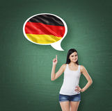 Woman is pointing out the thought bubble with German flag. Green chalk board background. Stock Photo