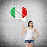 Woman is pointing out the thought bubble with Italian flag. Concrete background. Beautiful woman is pointing out the thought bubble with Italian flag. Concrete royalty free stock images