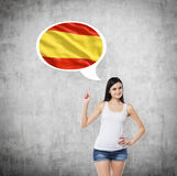 Woman is pointing out the thought bubble with Spanish flag. Concrete background. Royalty Free Stock Photos