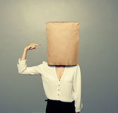 Woman pointing at paper bag on the head. Over dark background stock photo