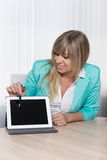 Woman is pointing with a pen to a tablet. Smiling businesswoman is pointing with a pen to a tablet while sitting at a table in the office. The woman is looking Stock Photo