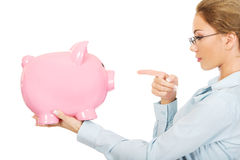 Woman pointing on piggy bank. Royalty Free Stock Photography