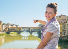 Woman pointing on ponte vecchio in florence, italy Stock Photo