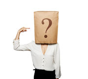 Woman pointing at question. Businesswoman with paper bag on the head pointing at question over white background royalty free stock images