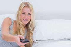 Woman pointing remote control at the camera Royalty Free Stock Photography