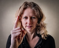 Woman pointing with a serious face Stock Image