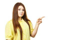 Woman pointing, serious face expression. Young woman pointing with finger at copy space with very serious face expression. Isolated on white royalty free stock photo