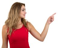 Woman pointing at sign. Young beautiful sexy woman showing copy space on empty blank sign or gift card. Royalty Free Stock Image