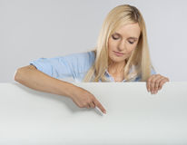 Woman pointing at a signboard. Woman pointing at a blank signboard Stock Photos
