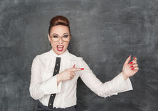 Woman pointing on something in her hand. Beautiful fashion woman pointing on something in her hand on the blackboard background Royalty Free Stock Photos
