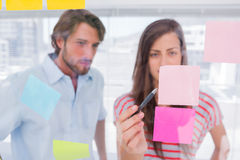 Woman pointing a sticky note. With her pen royalty free stock photo