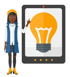 Woman pointing at tablet computer with light bulb. An african-american woman standing and pointing at a big tablet computer with a light bulb on a screen vector Royalty Free Stock Image