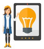 Woman pointing at tablet computer with light bulb. A woman standing and pointing at a big tablet computer with a light bulb on a screen vector flat design Royalty Free Stock Photos
