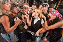 Woman Pointing at Thugs in Bar. Female nerd with husband confronting biker gang thugs in bar Stock Photography