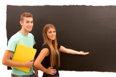 Woman pointing to the blackboard and man with book standing Stock Image