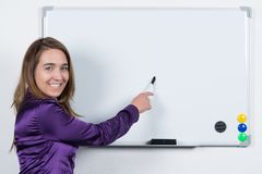 Woman is pointing to a board with a pen Royalty Free Stock Photos