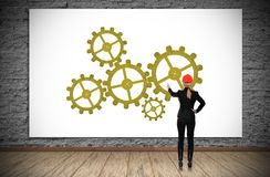 Woman pointing to cogs Royalty Free Stock Images
