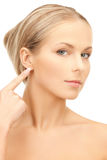 Woman pointing to ear Royalty Free Stock Photo