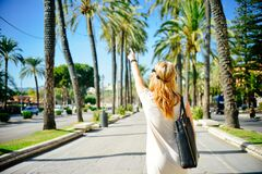 Woman pointing to palm tree Stock Photos