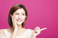 Woman pointing to somewhere, isolated on pink background Stock Images
