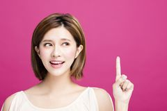 Woman pointing to somewhere, isolated on pink background Royalty Free Stock Photo