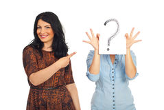 Woman pointing to unknown friend. Happy smiling woman pointing to her unknown friend who hold a question mark in front of face isolated on white background Royalty Free Stock Photos