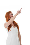 Woman pointing to the upper righthand corner. Attractive young woman pointing to the upper righthand corner of the frame and blank copyspace, isolated on white Royalty Free Stock Photo