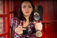Woman pointing to a vintage telephone handset Stock Image
