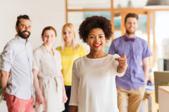 Woman pointing to you over creative office team Royalty Free Stock Photo