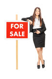 Woman pointing towards a for sale sign. Isolated on white background Royalty Free Stock Photo
