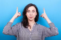 Woman pointing up with both hands. In studio photo on blue background Royalty Free Stock Photography