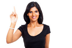 Woman pointing up. Close up portrait of happy indian woman pointing up against white background Royalty Free Stock Photo