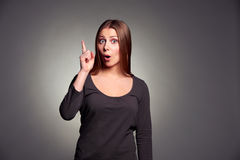 Woman pointing up and looking at camera Royalty Free Stock Images