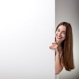 Woman pointing on white billboard over grey Royalty Free Stock Image