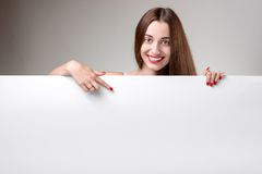 Woman pointing on white billboard over grey Stock Photo