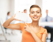 Woman pointing at white blank card in office Stock Photo