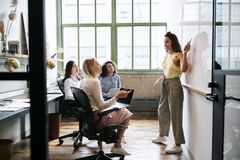 Woman pointing at whiteboard in a meeting with female team stock images