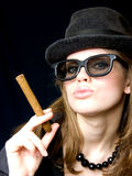 Woman in points and with a cigarette. Graceful lady in a hat and a cigarette in a hand Royalty Free Stock Image