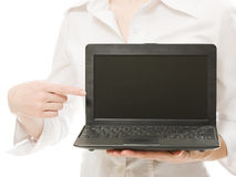 The woman points his finger on a laptop. Royalty Free Stock Photos