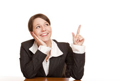 Woman points and looks up at blank ad space Royalty Free Stock Photography