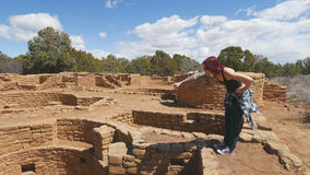 Woman Points at Something in a Kiva. A stands on the edge of a kiva at Mesa Verde National Park. She is leaning forward and pointing down into the kiva stock image