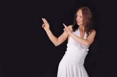 Woman points to copy space. Cute woman pointing to copy space, on dark background Stock Photo