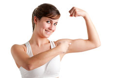 Woman Poiting at her Bicep. Woman smilling and pointing at her bicep after an workout, isolated in a white background Royalty Free Stock Images