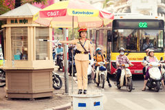 A woman police officer controls traffic on a busy street in Hanoi city Royalty Free Stock Image