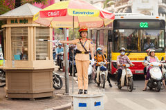 A woman police officer controls traffic on a busy street in Hanoi city Royalty Free Stock Photos