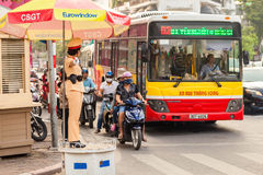 A woman police officer controls traffic on a busy street in Hanoi city Stock Photography