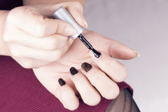 Woman polish her nails Stock Images