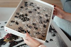 Woman with polish nails is making a puzzle stock images