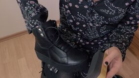 Woman polishing boots. In room stock video footage